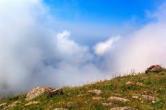 Στα βουνά επάνω από τα σύννεφα και το μπλε ουρανό Στοκ Φωτογραφίες