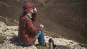 Στα βουνά κάθεται ένα άτομο σε ένα καπέλο κάουμποϋ, ένα σακάκι, το τζιν παντελόνι και τα γυαλιά δέρματος Ένα τσάι κατανάλωσης ατό φιλμ μικρού μήκους