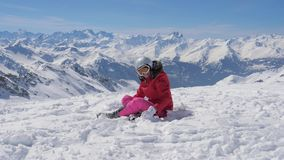 Στα βουνά ο ευτυχής θηλυκός σκιέρ ρίχνει επάνω στο χιόνι φιλμ μικρού μήκους