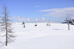 Στα βουνά, στις Άλπεις, οι σκιέρ αναρριχούνται επάνω chairlifts για να πάνε στις κλίσεις σκι στοκ εικόνα με δικαίωμα ελεύθερης χρήσης