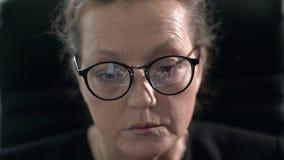 Στα γυαλιά της ώριμης γυναίκας μια γραφική παράσταση νομίσματος επιδεικνύεται ενώ μελετά τα χρηματιστήρια απόθεμα βίντεο