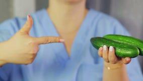 Στα θηλυκά πράσινα αγγούρια χεριών Ένα χέρι δείχνει σε τους απόθεμα βίντεο