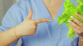 Στα θηλυκά φύλλα μαρουλιού χεριών Ένα χέρι δείχνει σε τον φιλμ μικρού μήκους