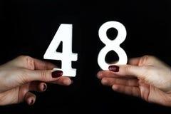 Στα θηλυκά χέρια ο αριθμός σαράντα οκτώ στοκ εικόνα με δικαίωμα ελεύθερης χρήσης