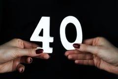 Στα θηλυκά χέρια ο αριθμός σαράντα στοκ φωτογραφία