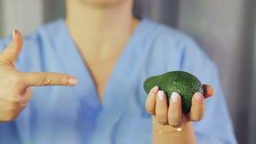 Στα θηλυκά χέρια, τα φρούτα του αβοκάντο Ένα χέρι δείχνει σε τον απόθεμα βίντεο