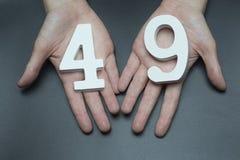 Στα θηλυκά χέρια ο αριθμός σαράντα εννέα στοκ εικόνες
