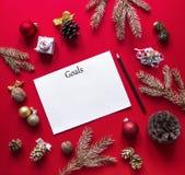 Στα κόκκινα Χριστούγεννα υποβάθρου οι διακοσμήσεις και οι κομψοί χρυσοί κλάδοι τακτοποιούνται, και στο κέντρο βρίσκεται στόχοι άσ Στοκ φωτογραφία με δικαίωμα ελεύθερης χρήσης