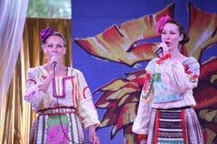 Στα σκηνικά όμορφα κορίτσια στα εθνικά ρωσικά κοστούμια, εσθήτες sundresses με τη δονούμενη κεντητική - ομάδα φολκλορικής μουσική Στοκ Εικόνα