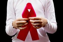 Στα χέρια παιδιών η κόκκινη κορδέλλα ενισχύσεων Στοκ Φωτογραφίες