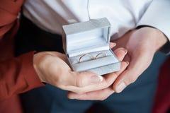 Στα χέρια των δαχτυλιδιών newlyweds σε ένα κιβώτιο Στοκ φωτογραφία με δικαίωμα ελεύθερης χρήσης