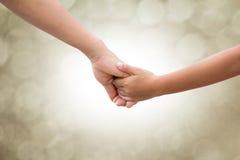 Στα χέρια των γονέων και των παιδιών σε μια θαμπάδα υποβάθρου bokeh Μητέρα που συλλαμβάνεται για τον τόνο σεπιών ύφους προσοχής μ Στοκ Φωτογραφία