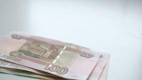 Στα χρήματα αρίθμησης Πτώσεις χρημάτων σε έναν άσπρο πίνακα Οι άνθρωποι δίνουν γρήγορα ρίχνουν τα ρωσικά nominals 200 και 100 τρα απόθεμα βίντεο