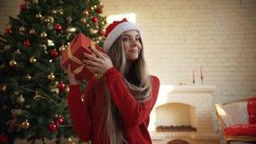 Στα Χριστούγεννα, ένα όμορφο κορίτσι βρήκε ένα δώρο κάτω από το δέντρο Έννοια: μαγικός, Χριστούγεννα, δώρο, διακοπές απόθεμα βίντεο