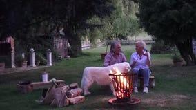 Στα ψημένα στη σχάρα λουκάνικα οι ελκυστικοί σύζυγοι πίνουν ένα γαλλικό ροδαλό κρασί απόθεμα βίντεο