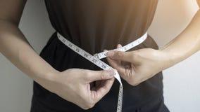 Στενές επάνω γυναίκες έννοιας διατροφής που μετρούν την περιφέρεια μέσης στοκ φωτογραφία
