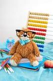 στενές σχολικές προμήθειες μοιρογνωμόνιων πυξίδων επάνω Το Teddy αντέχει με τα γυαλιά Στοκ Φωτογραφία