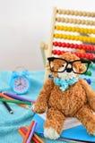 στενές σχολικές προμήθειες μοιρογνωμόνιων πυξίδων επάνω Το Teddy αντέχει με τα γυαλιά Στοκ Εικόνες