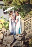 Στενές φίλες bestie στο κινεζικό παραδοσιακό αρχαίο κοστούμι σε έναν κήπο στοκ εικόνες