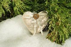στενή άνοιξη Ένα χιόνι-λειώνοντας υπόβαθρο χιονιού με το πράσινο κυπαρίσσι διακλαδίζεται με μια χειροποίητη καρδιά στοκ εικόνες