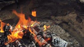 Στενή άποψη στον καμμένος ξυλάνθρακα και τη φλόγα στη σχάρα σχαρών