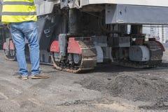 Στενή άποψη σχετικά με τους εργαζομένους και τις ασφαλτώνοντας μηχανές Μηχανήματα για τους δρόμους στοκ εικόνες