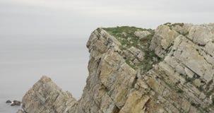 Στενή άποψη της κορυφής ενός απότομου βράχου με τη θάλασσα στον ορίζοντα φιλμ μικρού μήκους