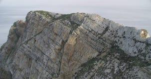 Στενή άποψη της κορυφής ενός απότομου βράχου με τη θάλασσα στον ορίζοντα απόθεμα βίντεο