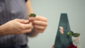 Στενή άποψη του ανθοκόμου που κάνει τη σύνθεση λουλουδιών μέσα στο γραφείο απόθεμα βίντεο