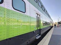 Στενή άποψη του πράσινου τραίνου που φθάνει αφήνοντας την πλατφόρμα σταθμών τρένου Τρόπος περπατήματος ατόμων από το σταθμό στοκ εικόνα