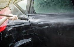στενή έννοια καθαρότητας αυτοκινήτων επάνω στην πλύση Το καθαρίζοντας αυτοκίνητο που χρησιμοποιεί υψηλό νερό από τη γυναίκα, γυνα Στοκ Εικόνες