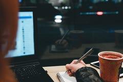 Στενή επάνω εκμετάλλευση χεριών κοριτσιών μια μάνδρα, που γράφει σε ένα σημειωματάριο, lap-top στον καφέ, smartphone, μάνδρα, υπο στοκ εικόνες