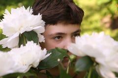 Στενή επάνω φωτογραφία αγοριών εφήβων με τα άσπρα peony λουλούδια Στοκ φωτογραφίες με δικαίωμα ελεύθερης χρήσης