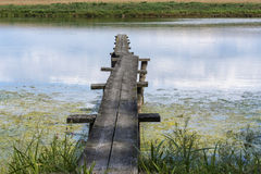 Στενή ξύλινη γέφυρα για πεζούς επάνω από το νερό λιμνών Στοκ εικόνες με δικαίωμα ελεύθερης χρήσης