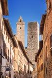 21 04 2017 - Στενή οδός μέσω του SAN Giovani και πύργος Cuganensi στο SAN Gimignano, Τοσκάνη Στοκ Εικόνες