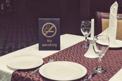 Στεναγμός απαγόρευσης του καπνίσματος στον πίνακα με τα γυαλιά, την πετσέτα και τα πιάτα στο εστιατόριο στοκ εικόνες με δικαίωμα ελεύθερης χρήσης