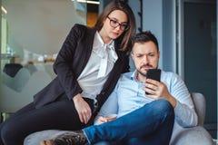 Στενοί συνάδελφοι που εξετάζουν το κινητό τηλέφωνο κατά τη διάρκεια του σπασίματος στοκ φωτογραφία