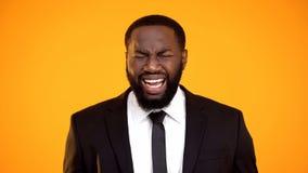 Στενοχωρημένος μαύρος επιχειρηματίας που κάνει τον επίπονο μορφασμό, που χάνει προσοδοφόρα τη διαπραγμάτευση στοκ φωτογραφία