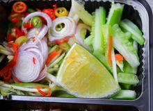 Στενός επάνω κομματιού λεμονιών στο λαχανικό στο Μαύρο κιβωτίων Στοκ Εικόνες
