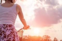 Στενός επάνω κοριτσιών με το ποδήλατο στο θερινό ηλιοβασίλεμα στο δρόμο στο πάρκο πόλεων Ανακύκλωση κάτω από την οδό για να εργασ στοκ εικόνες με δικαίωμα ελεύθερης χρήσης