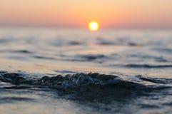 Στενός επάνω κυμάτων θάλασσας στο χρόνο ηλιοβασιλέματος με την κόκκινη και πορτοκαλιά αντανάκλαση ήλιων στο νερό Θολωμένη περίληψ Στοκ Φωτογραφίες