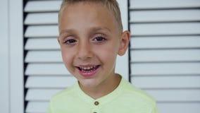 Στενός επάνω πορτρέτου προσώπου Όμορφο μικρό παιδί που εξετάζει τη κάμερα και που χαμογελά ευγενικά Απομονωμένη άσπρη ανασκόπηση  απόθεμα βίντεο