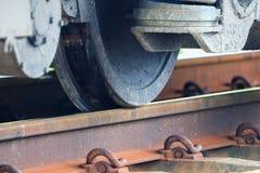 Στενός επάνω ροδών τραίνων στη διαδρομή σιδηροδρόμων στο σταθμό στοκ εικόνες