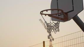 Στενός επάνω στεφανών καλαθοσφαίρισης στο ηλιοβασίλεμα και τη σημειωμένη σφαίρα απόθεμα βίντεο