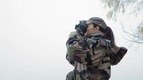 Στενός - επάνω, όμορφη γυναίκα στην κάλυψη στρατού που κοιτάζει μέσω των διοπτρών στην όχθη ποταμού στην ομίχλη απόθεμα βίντεο