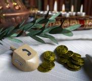 Στενός επάνω Hanukkah με τα κεριά, τα περιστρεφόμενα τοπ και χρυσά παλαιά νομίσματα Στοκ Φωτογραφίες