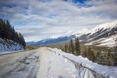 Στενός και ολισθηρός χειμερινός δρόμος με τα μεγάλα snowbanks που κάμπτουν κάτω από το βουνό, εθνικό πάρκο Banff, Καναδάς Στοκ Εικόνες