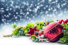 στενός κόκκινος χρόνος Χριστουγέννων ανασκόπησης επάνω Η κάρτα Χριστουγέννων με το έλατο σφαιρών και το ντεκόρ ακτινοβολούν επάνω Στοκ Εικόνα
