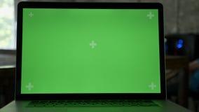 Στενός πυροβολισμός της επίδειξης lap-top ` s με το chromakey στο σύγχρονο γραφείο απόθεμα βίντεο