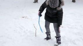 Στενός πυροβολισμός του μικρού κοριτσιού που τρέχει στο λόφο στο χειμερινό πάρκο απόθεμα βίντεο
